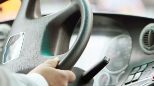 driver holding school bus steering wheel