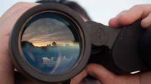 closeup of a person looking through binoculars